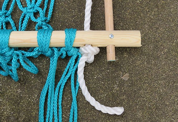String the rope through bottom of frame and tie a loose knot.