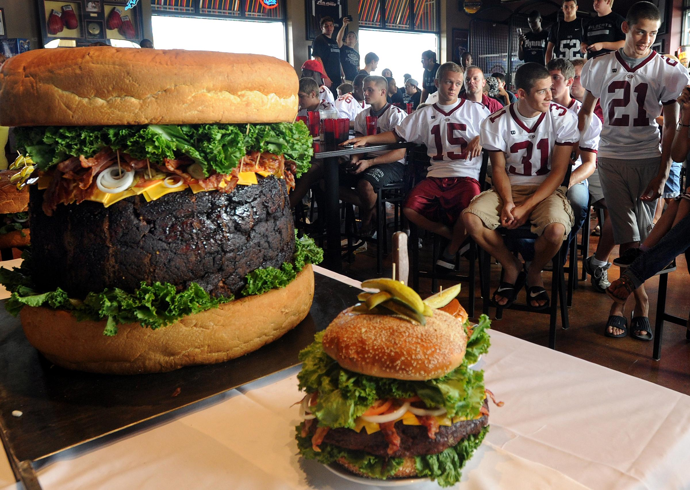A member of the Southgate Anderson High School football team attempts to eat his share of a 300-pound hamburger at Mallie's Sports Bar & Grill. (Photo by Dave Chapman)