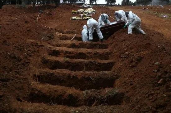 Coveiros vestindo roupas de proteção enterram o caixão de Jose Soares, 48 anos, que morreu da doença de coronavírus (COVID-19), no cemitério São Luiz, em São Paulo.