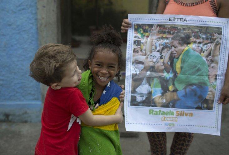 Друг обнимает четырехлетнюю Джовану Силву — кузину дзюдоистки Рафаэлы Силвы, выигравшей золото на Олимпийских играх в Рио. Снимок сделан 9 августа 2016 года в трущобах района Рио-де-Жанейро Сидаде-де-Деуш, в переводе означающего «Город Бога». Там выросла Силва. После победы она со слезами на глазах говорила: «Если бы не спорт, я до сих пор жила бы там». (Leo Correa / AP)