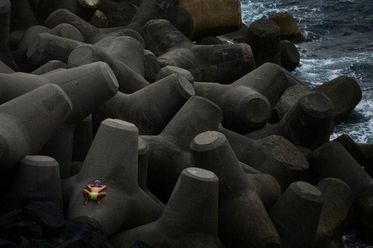Мальчик отдыхает на цементных блоках на маленьком вулканическом острове Стромболи, Италия, 16 июня 2016 года. (Gabriel Bouys / AFP / Getty)