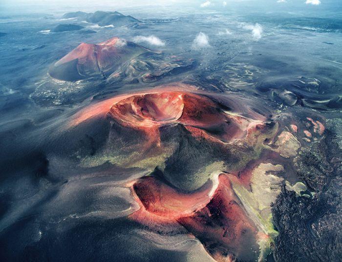 Кратеры с высоты птичьего полета. Красные породы проступают из-под слоя черного пепла, образуя пластичные узоры на поверхности земли.