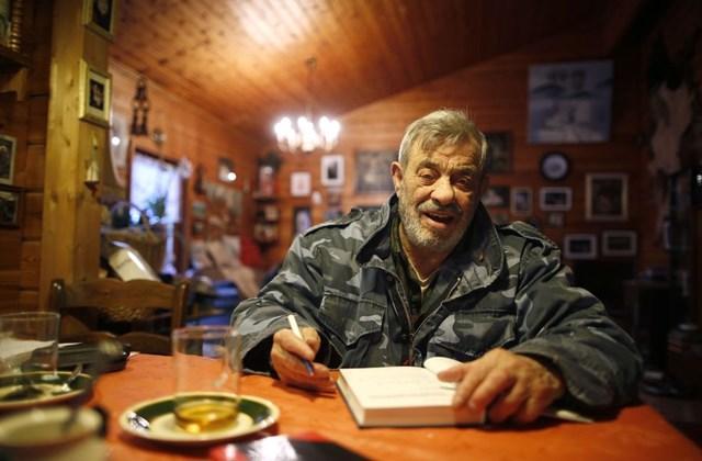 Мужчина, изучая волков, ест со стаей сырое мясо