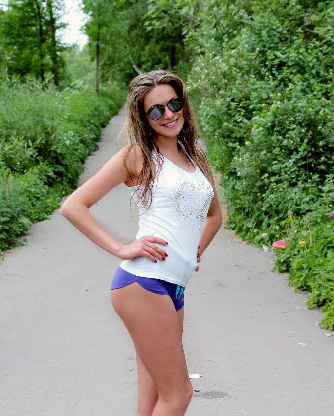 Спортивная девушка в топике бегает в парке