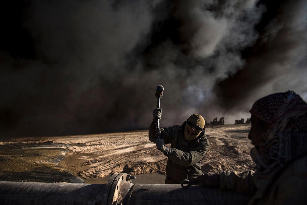 21. Почерневший от нефти иракский флаг. (Фото Goran Tomasevic | Reuters):