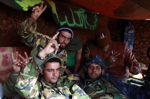 Rebel fighters pose while smoking a hashish cigarette in a tent near a tank along the road between Ajdabiyah and Brega