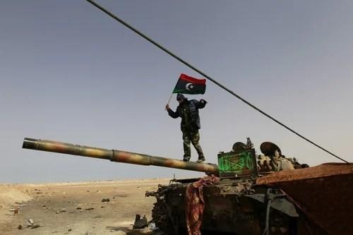 A rebel fighter walks on a tank along the road between Ajdabiyah and Brega