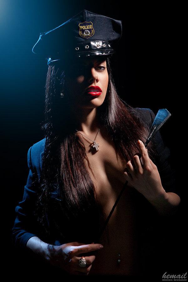 Брюнетка ню в форме полицейского с хлыстом
