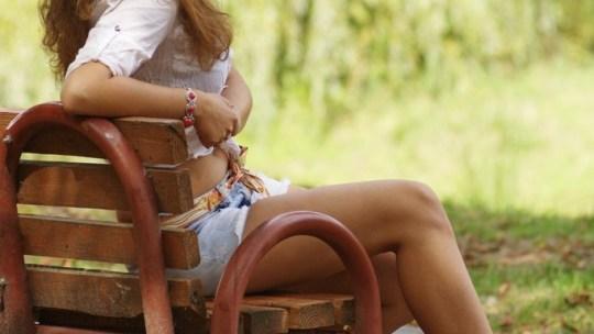 Рыжая дамочка в парке в мини-шортах