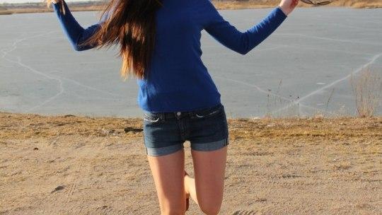 Красотка с длинными волосами в мини-шортах на каблуках