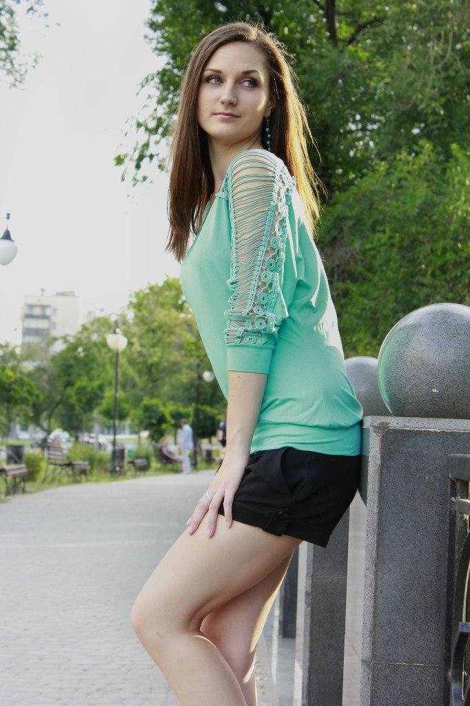 Девушка шатенка  в черных шортах в парке