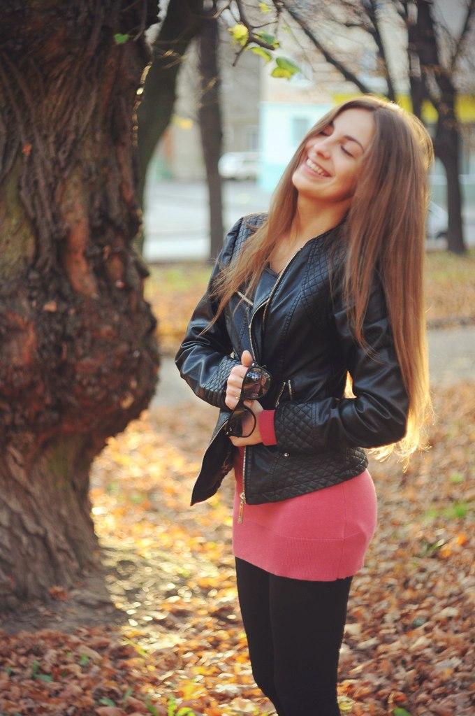 Девушка в осеннем лесу в кожаной куртке