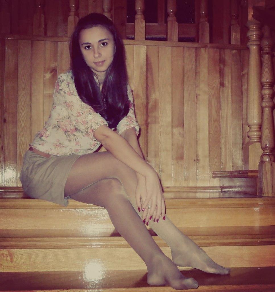 Девчонка на ступеньках в легкой кофточке и колготках