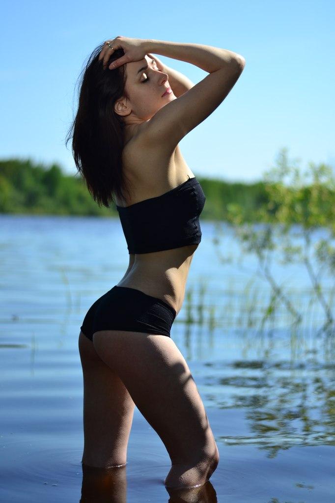 Фото со спины девушки в черном купальнике