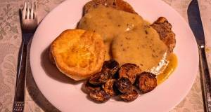 Fried pork chop in cognac gravy sauce with Yorkshire pudding and Baked Brussel Sprouts