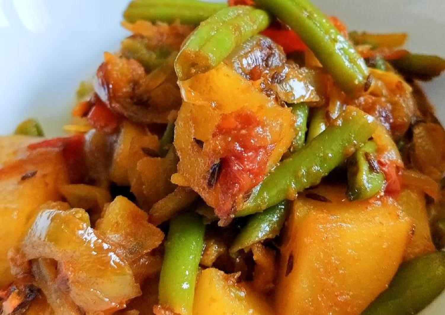 Stir Fry beans, potatoes and tomatoes in caramelized onions