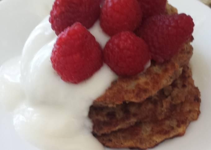 Vegan apple wheat pancake topped with yogurt and berries