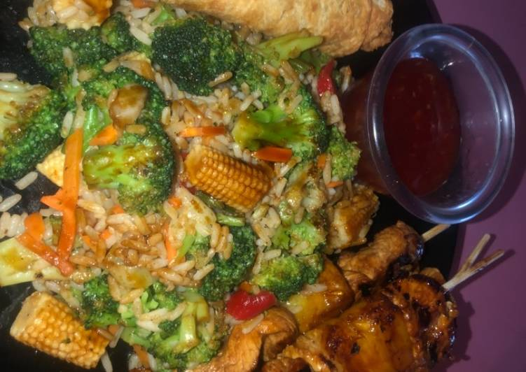 Teriyaki chicken and pineapple skewers with fried rice and veggies and eggs rolls