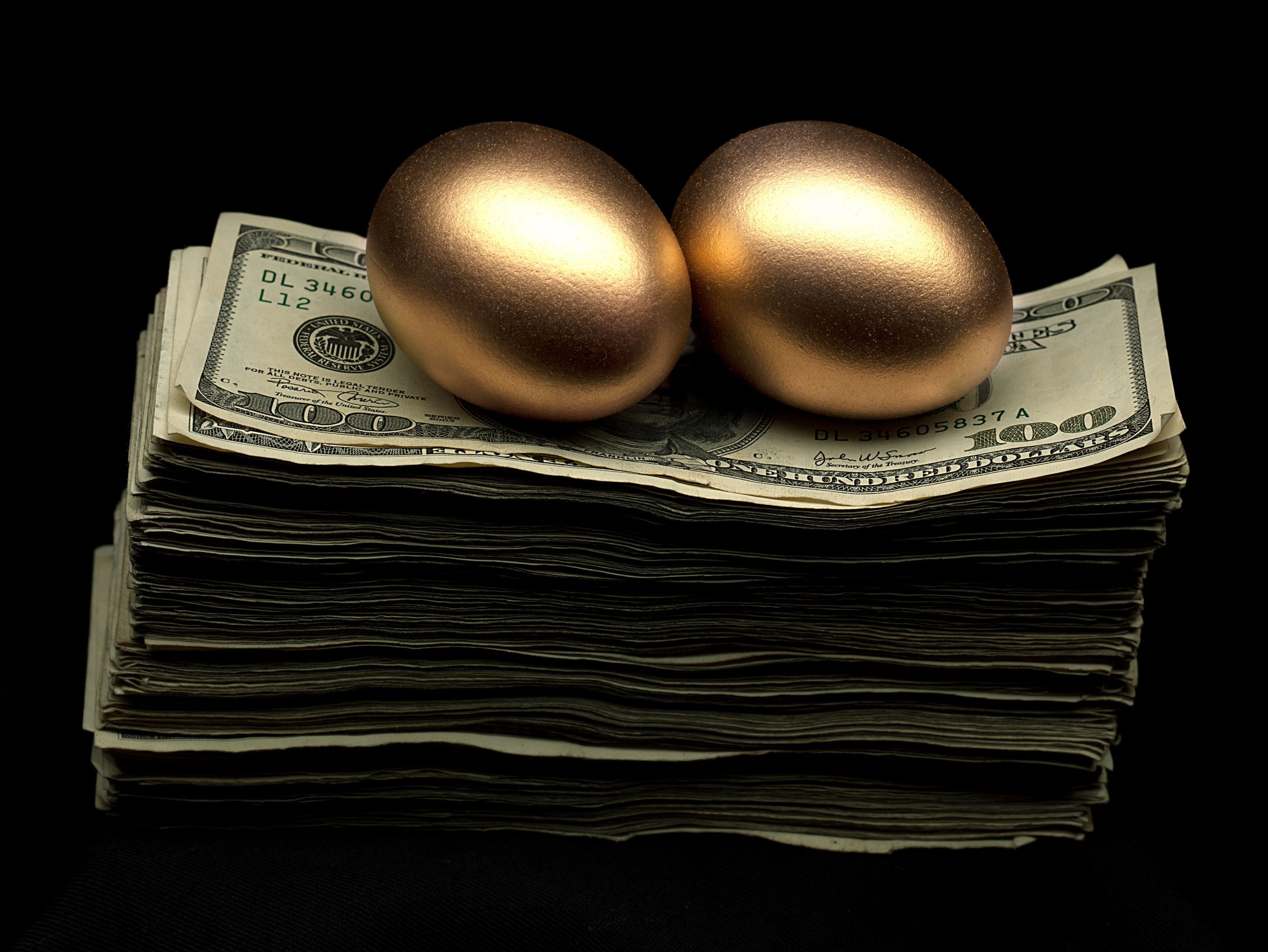 Two gold eggs on pile of cash. Adrianna Williams/Getty Images