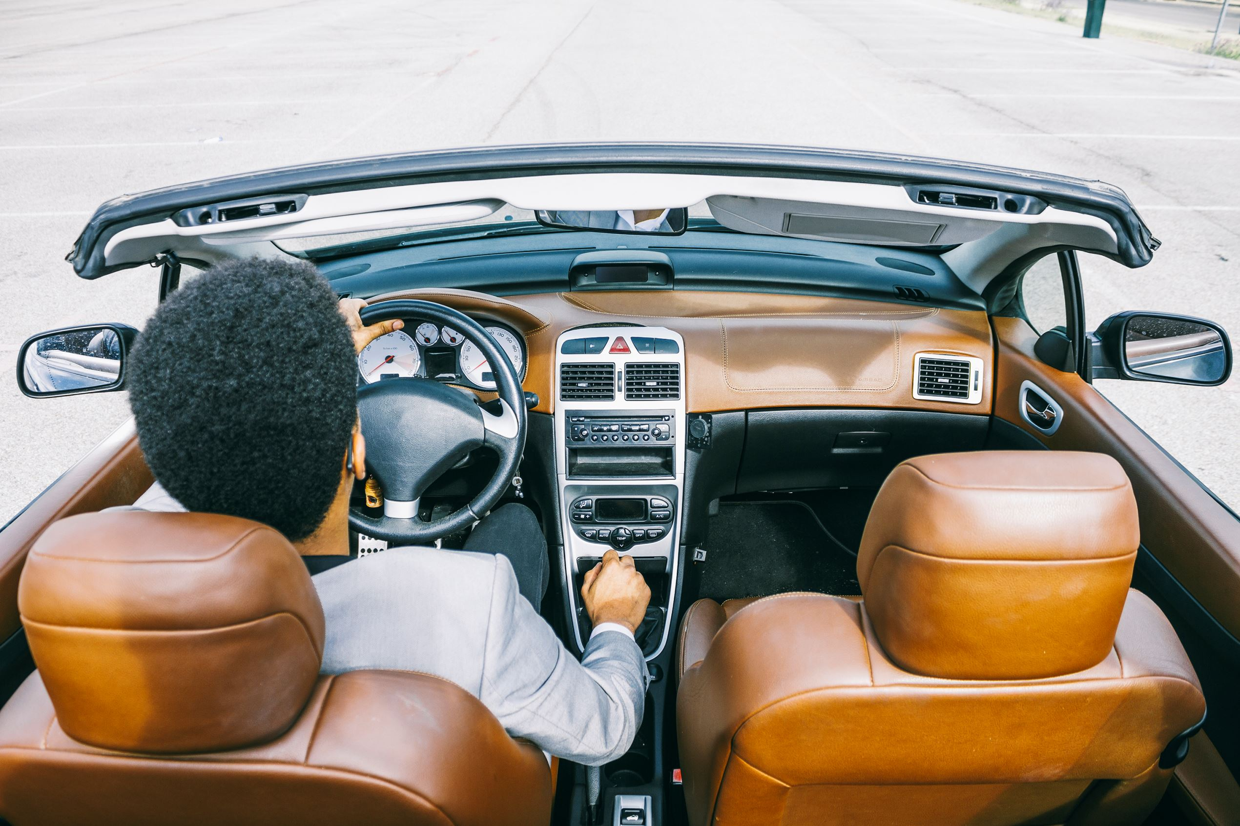 Young black man driving convertible