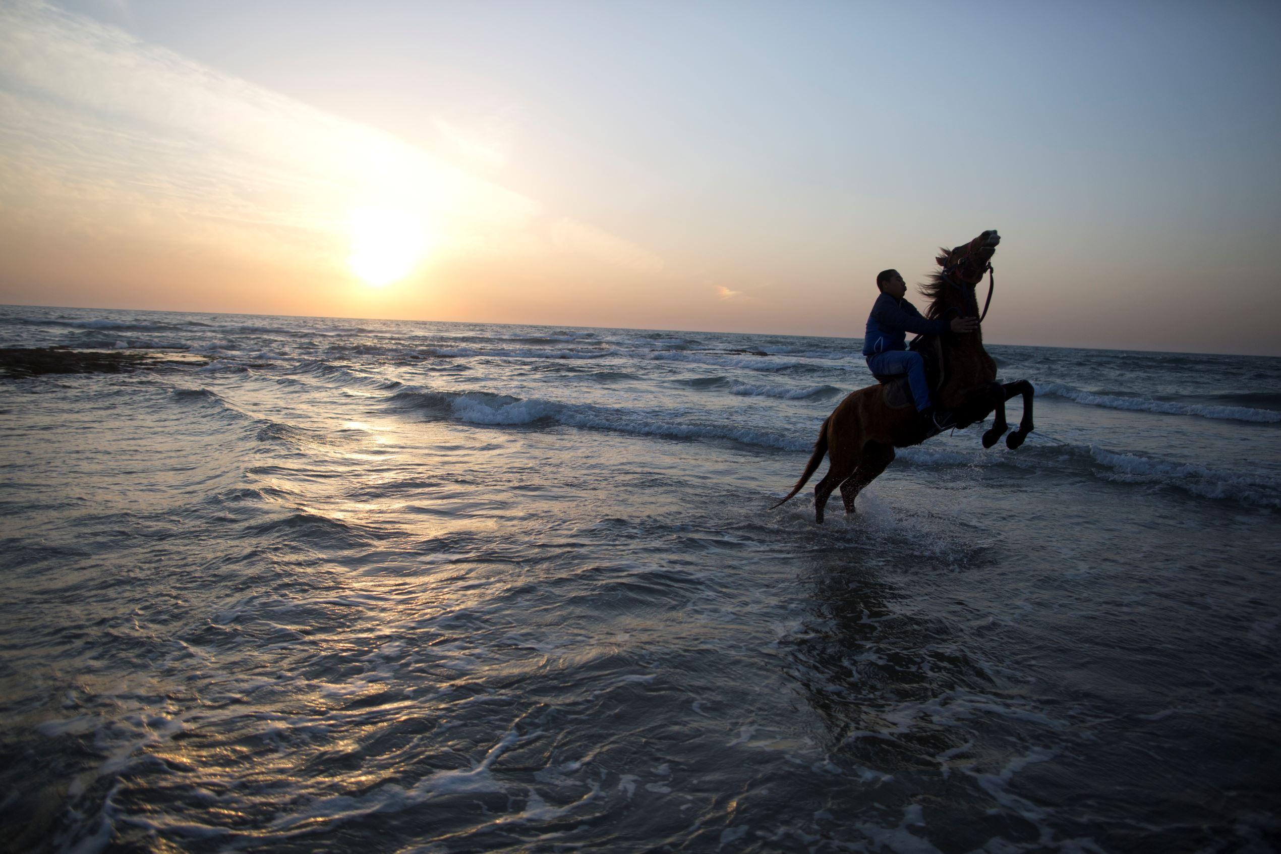Слайд 39 из 67: JISR AZ ZARQA, ISRAEL - MARCH 07:  An Arab Israeli man rides a horse on the beach  on March 7, 2016 in the Arab Israeli Town of Jisr az Zarqa, Israel.  Jisr az-Zarqa is the only remaining Arab town in Israel located on the coast of the Mediterranean Sea,