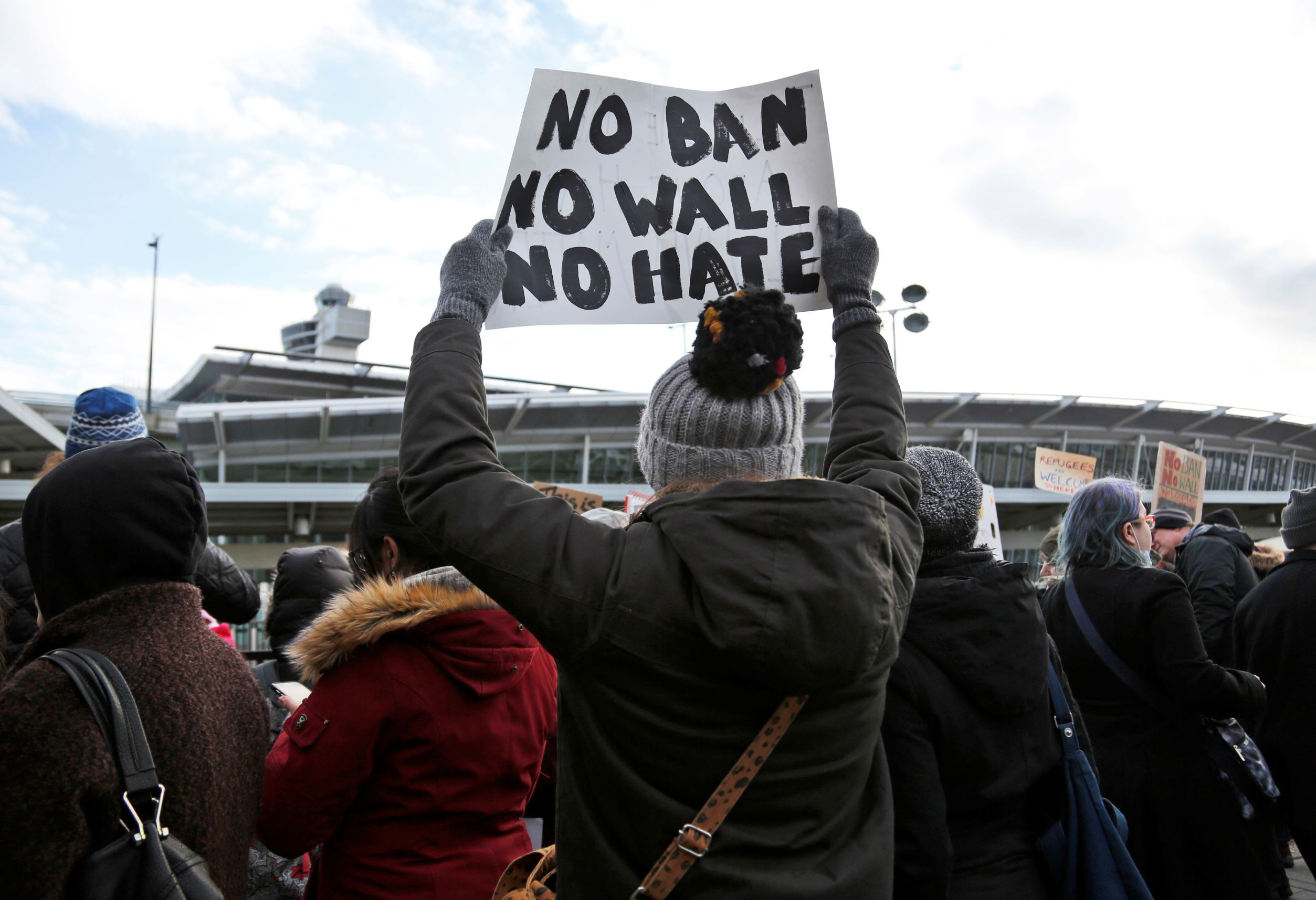 Slide 1 of 32: Protesters rally in front of John F. Kennedy International Airport in New York, Sunday, Jan. 29, 2017. President Donald Trump's immigration order sowed more chaos and outrage across the country Sunday, with travelers detained at airports, panicked families searching for relatives and protesters registering opposition to the sweeping measure that was blocked by several federal courts. (AP Photo/Seth Wenig)