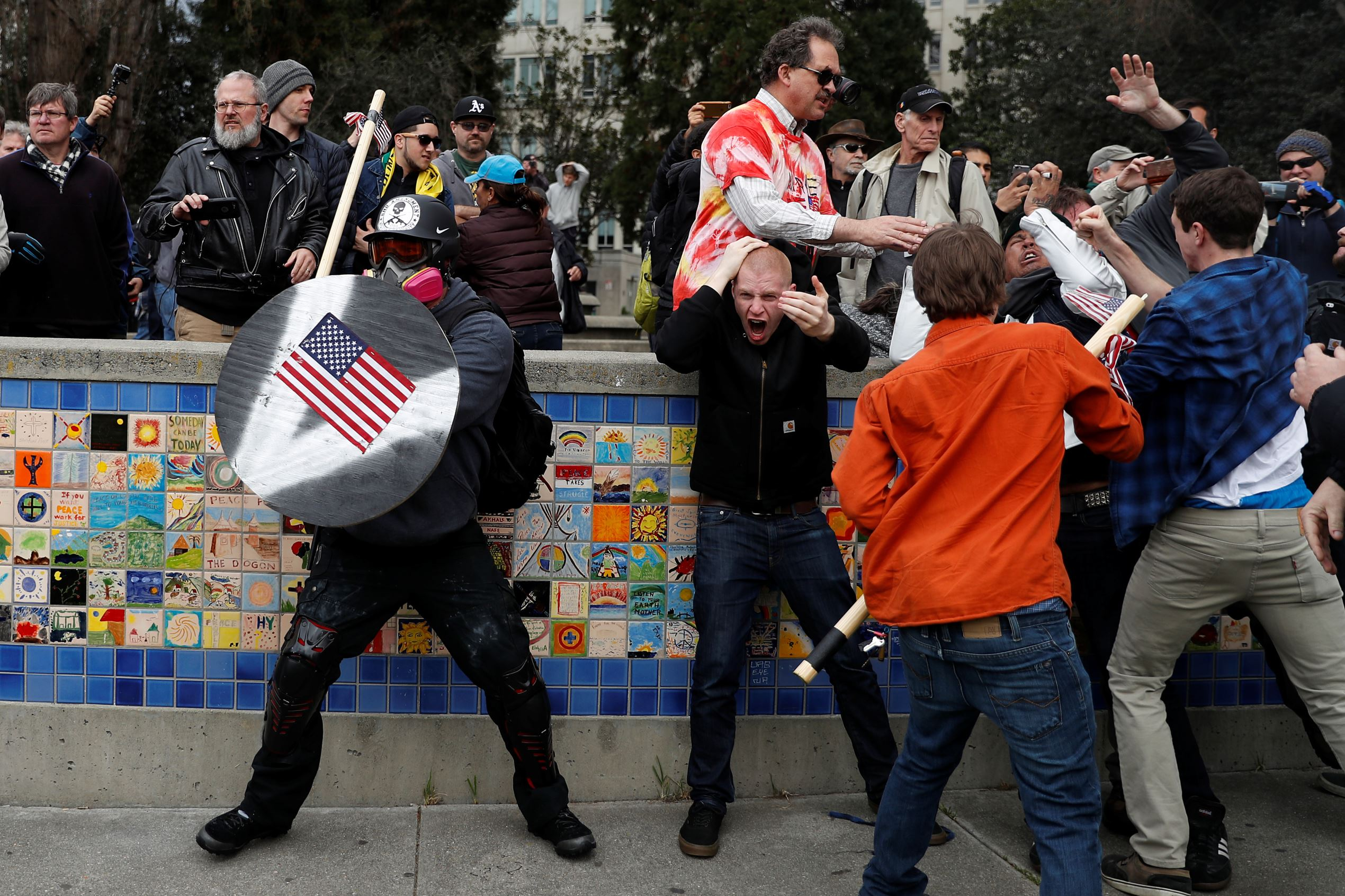 "A demonstrator supporting U.S. President Donald Trump (L) holds a shield as a group of men punch a counter demonstrator during a ""People 4 Trump"" rally in Berkeley, California March 4, 2017."