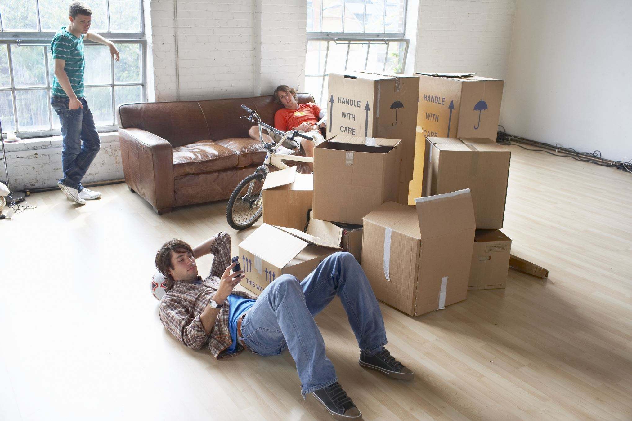 Three young men resting in new apartment after moving