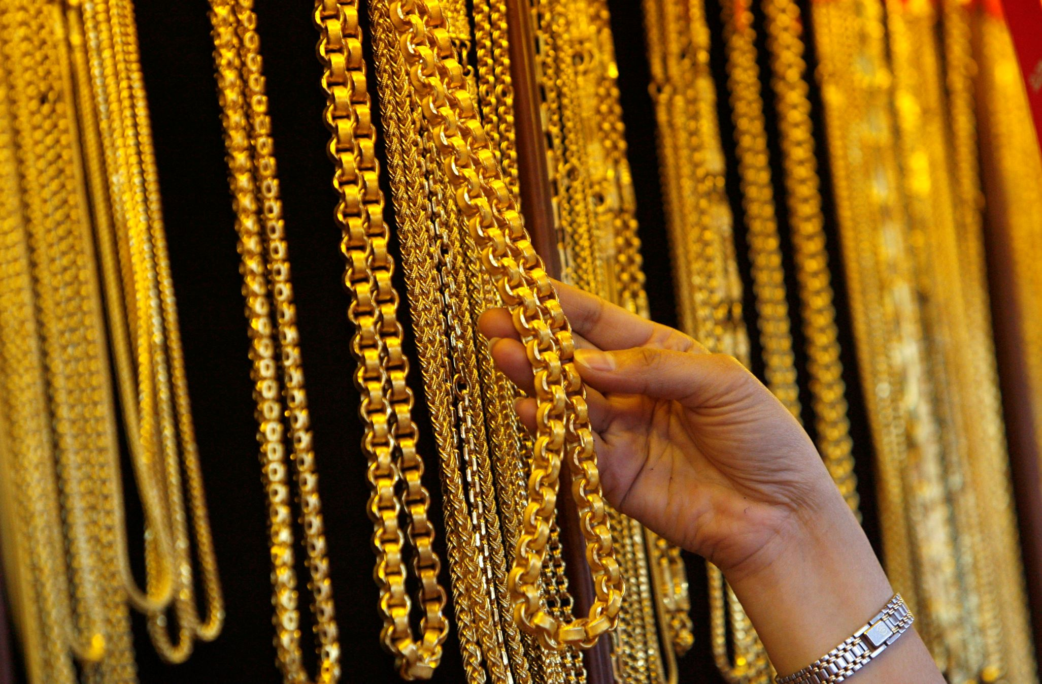 Shopkeeper inspecting gold jewelry.