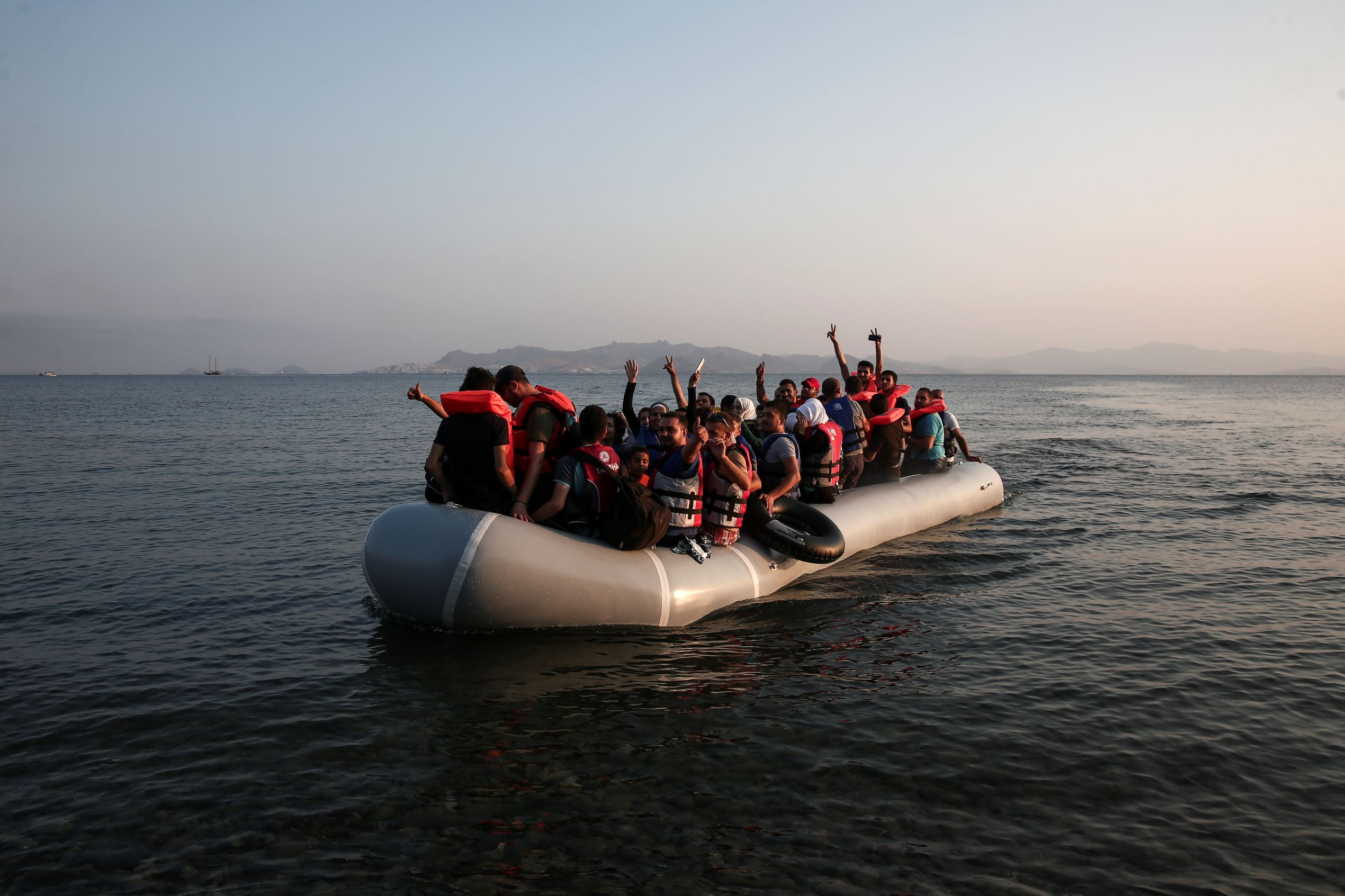 Migrants arrive at the coast on a dinghy after crossing from Turkey, at the southeastern island of Kos, Greece, Tuesday, Aug. 11, 2015. Fights broke out among migrants on the Greek island of Kos Tuesday, where overwhelmed authorities are struggling to contain increasing numbers of people arriving clandestinely on rubber dinghies from the nearby Turkish shore. (AP Photo/Yorgos Karahalis)