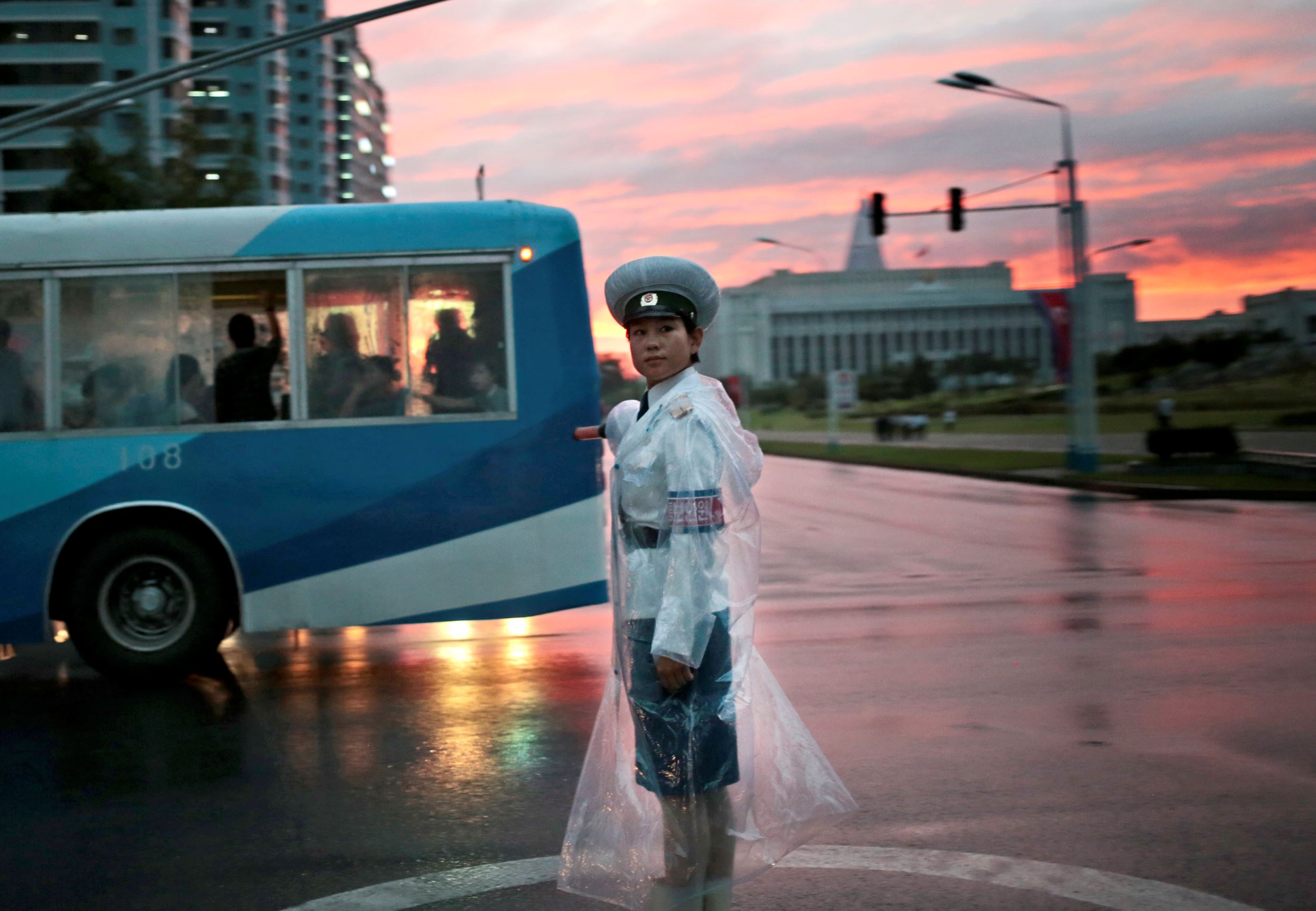 A traffic police officer directs vehicles at a street junction during sunset in Pyongyang, North Korea, on Aug. 25, 2016.