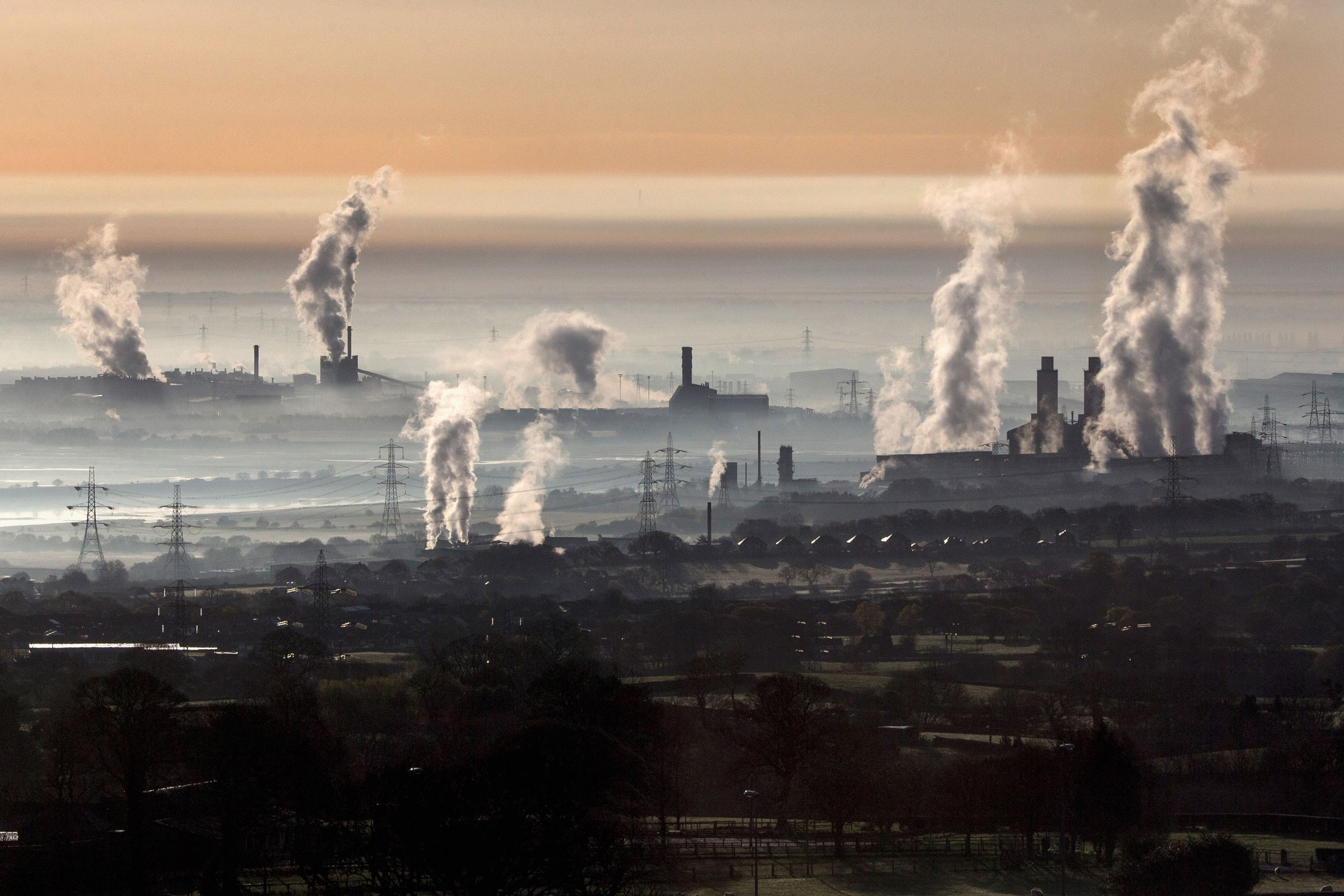 Слайд 35 из 86: FLINT, WALES - APRIL 13:  The industrial landscape across the Dee Estuary at sunrise as steam rises from Deeside power station, Shotton Steelworks and other heavy industrial plants on April 13, 2016 in Flint, Wales. The British Steel industry has been pl