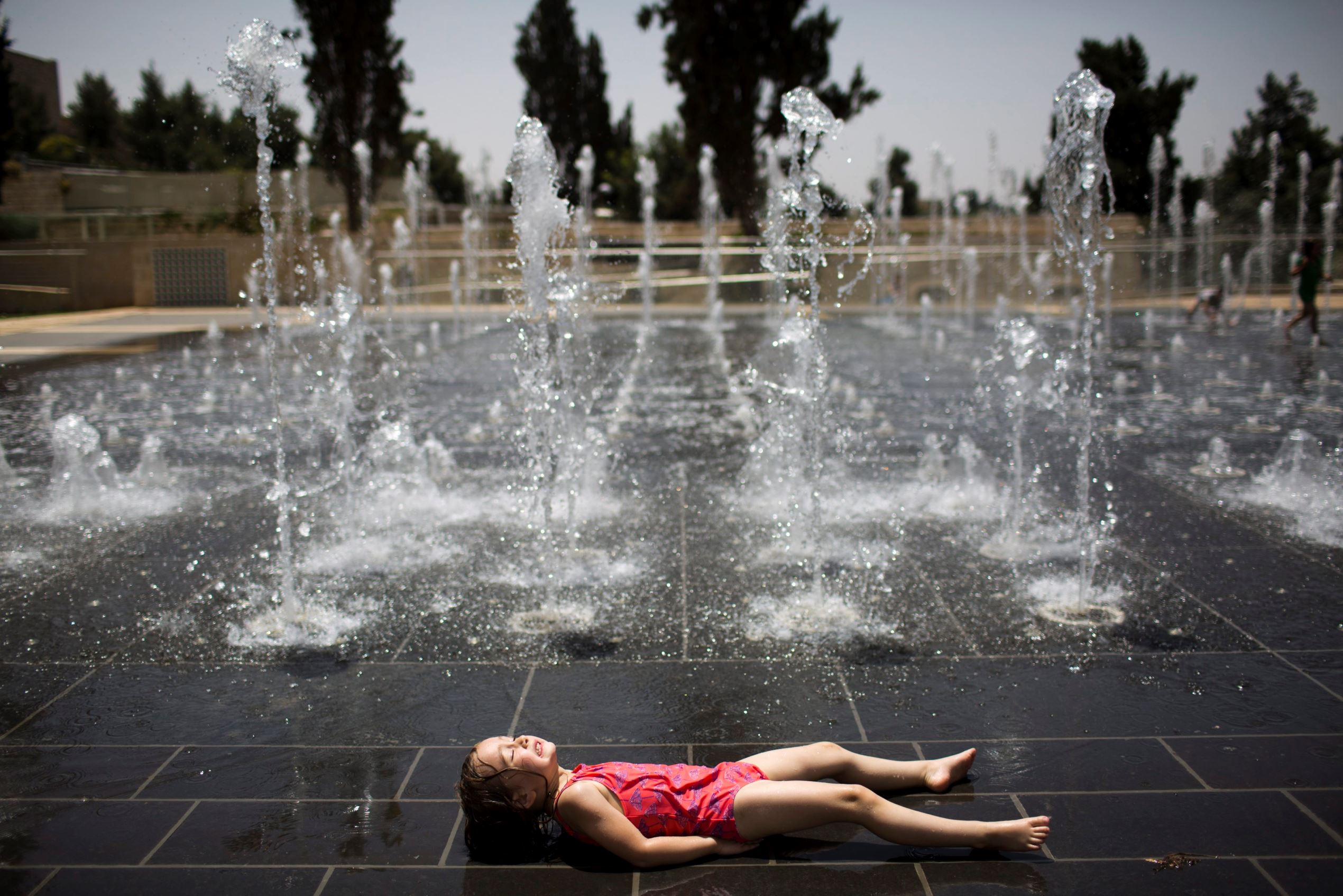 Слайд 47 из 86: epaselect epa05307553 An Israeli child plays in a water fountain on a hot day near the Tower of David in the Old City of Jerusalem, Israel, 15 May 2016. According to the Israeli Metereological Service, an intense heatwave has hit the country, with ...