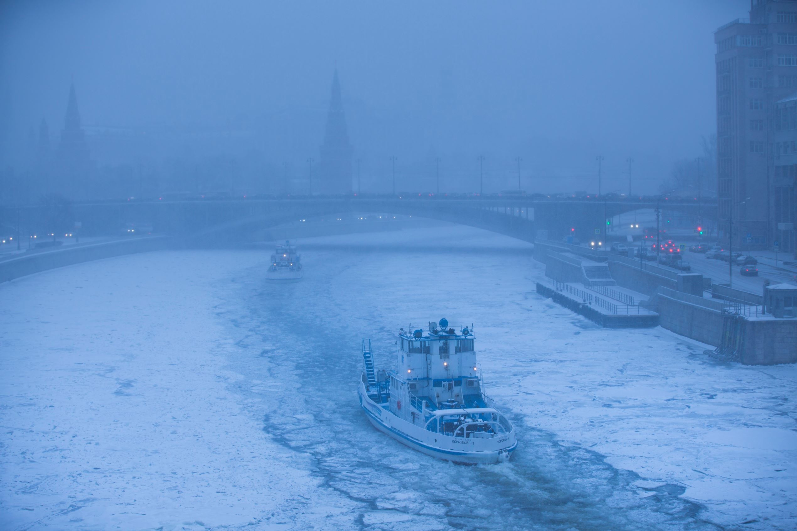 Слайд 7 из 86: Two ice breakers move along the frozen Moskva River with the Kremlin in the background during snowfall in Moscow, Russia, Tuesday, Jan. 12, 2016. Moscow was hit by a heavy snowfall Tuesday, which led to the cancellation of dozens of flights at the city a