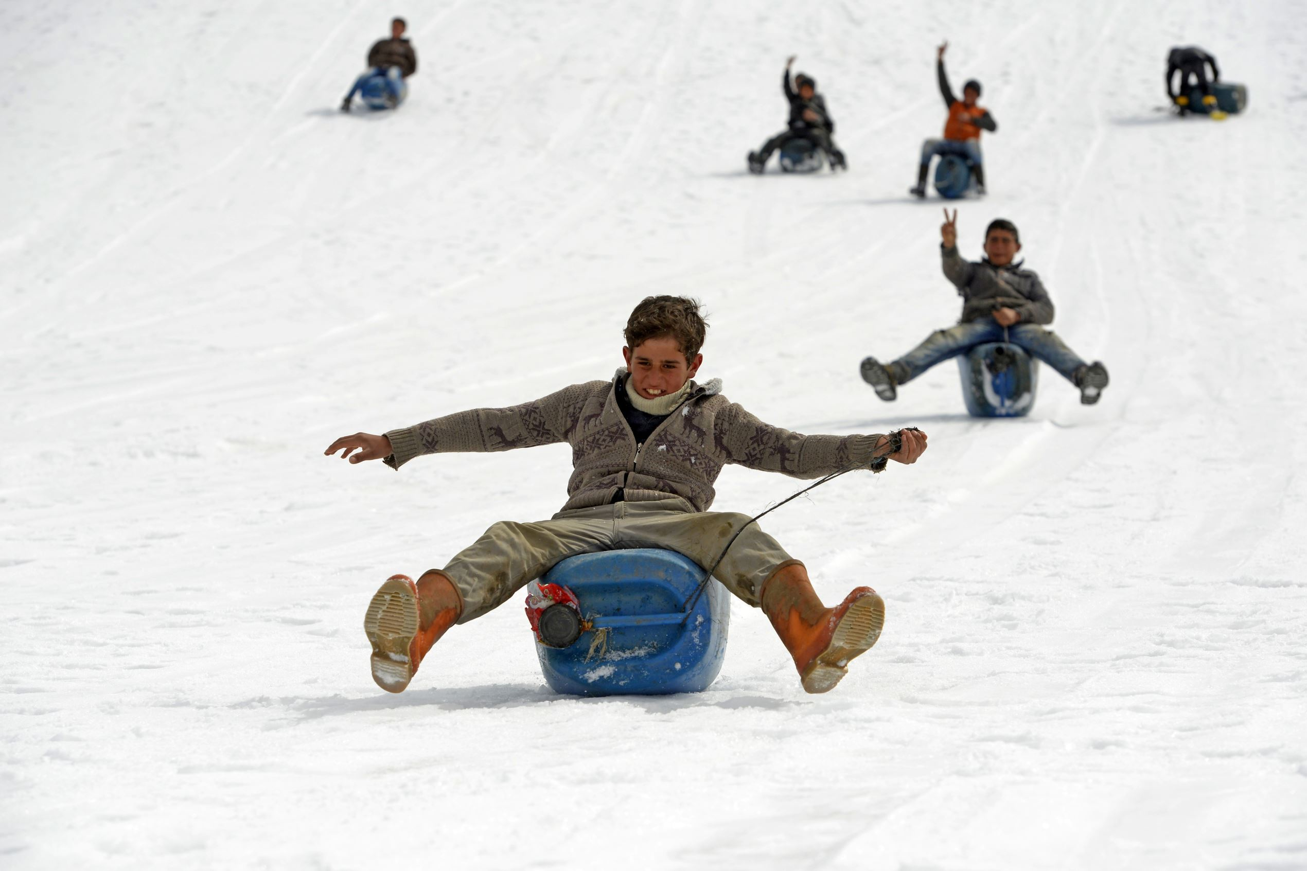 Слайд 27 из 86: VAN, TURKEY - MARCH 5: Youths slide down on snow-covered slope from the top of the hill at Yucelen neighborhood of Cilli district of Caldiran town in Van, Turkey on March 5, 2016. (Photo by Ozkan Bilgin/Anadolu Agency/Getty Images)