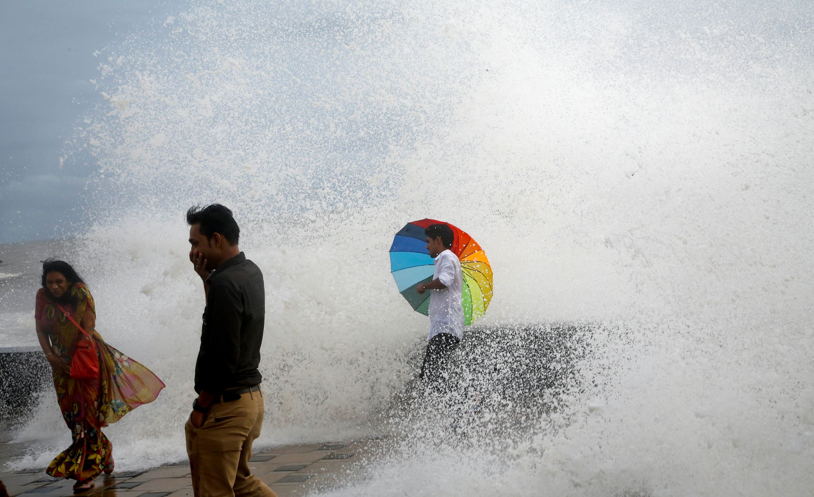Слайд 60 из 86: An Indian man holding an umbrella stands on the Arabia Sea coast as he enjoys the high tide waves in Mumbai, India, Wednesday, June 29, 2016. Monsoon rains have picked up pace in the city after a slow start, bringing welcome relief after a long drought.