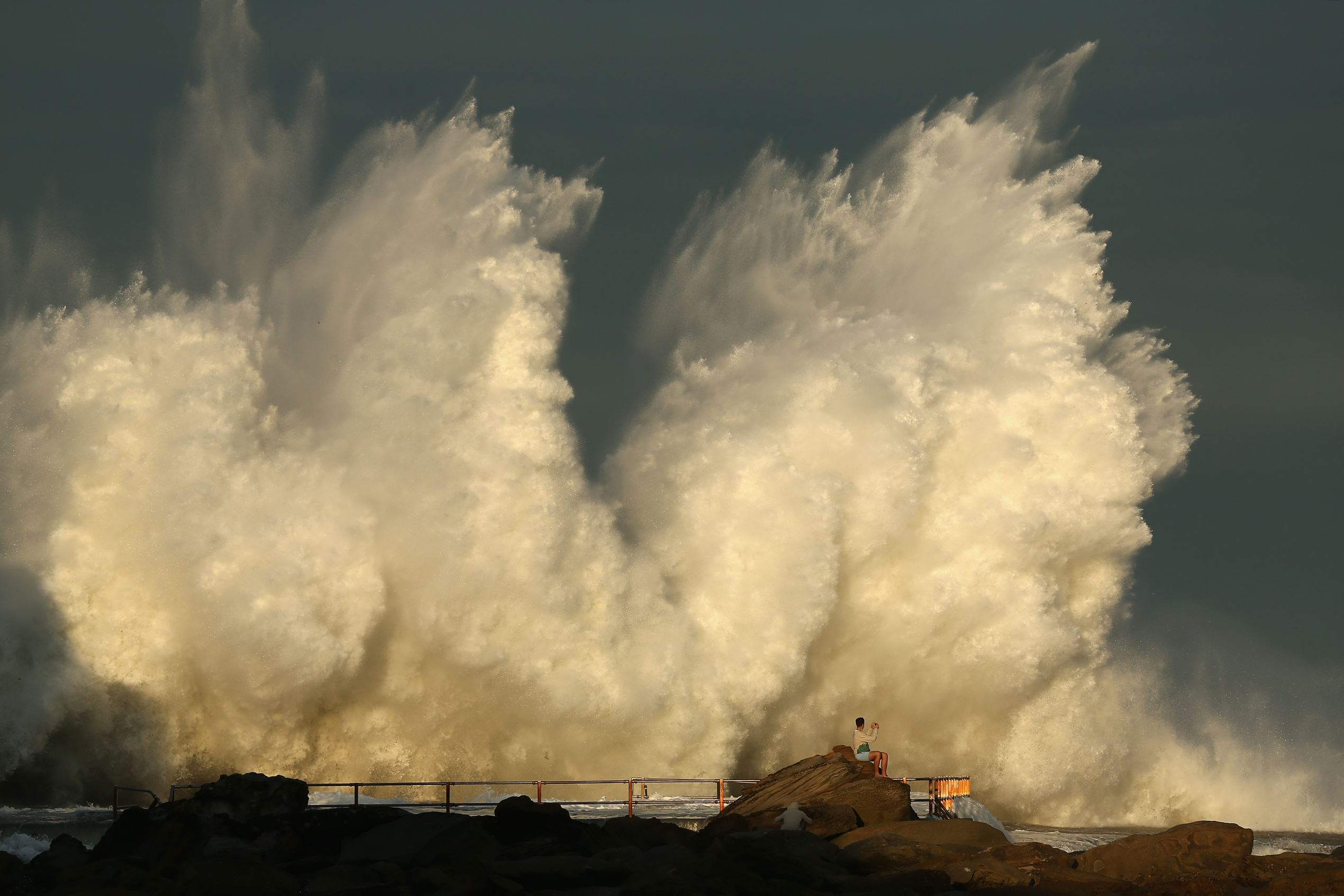 Слайд 53 из 86: SYDNEY, AUSTRALIA - JUNE 06:  A man watches a wave hit a rock pool at Curl Curl beach as large swell hits the East Coast of Australia on June 6, 2016 in Sydney, Australia. Torrential rain over the weekend saw streets and homes flooded while wind gusts up
