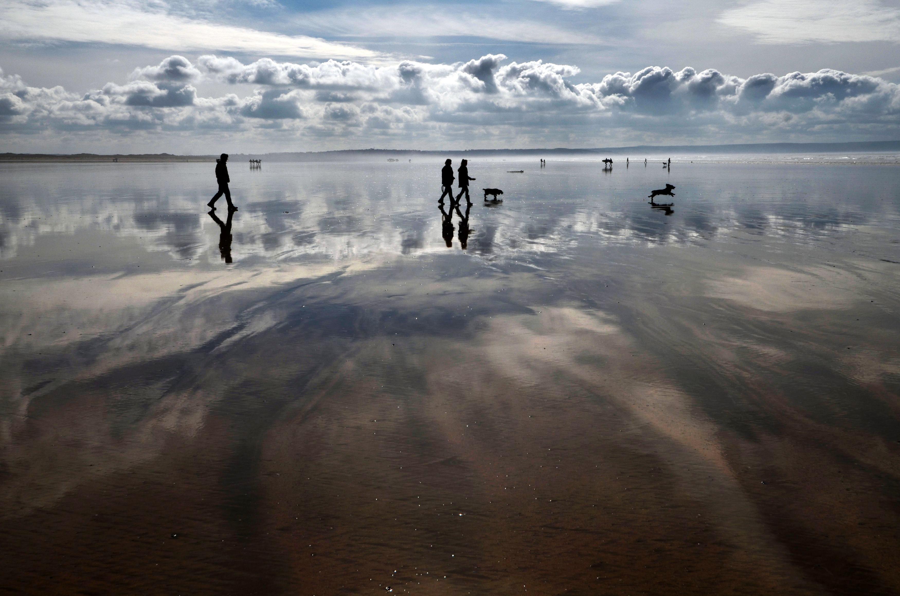 Слайд 29 из 86: Dog walkers silhouetted on the beach enjoy the mild weather at Saunton Sands, North Devon.