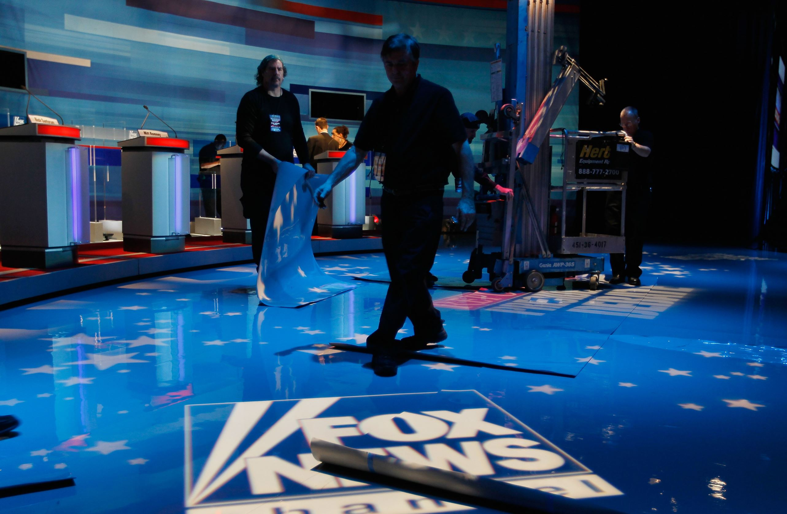 Workers prepare the stage for the Fox News/Wall Street Journal/South Carolina GOP debate at the Sheraton Myrtle Beach Convention Center on January 16, 2012 in Myrtle Beach, South Carolina.