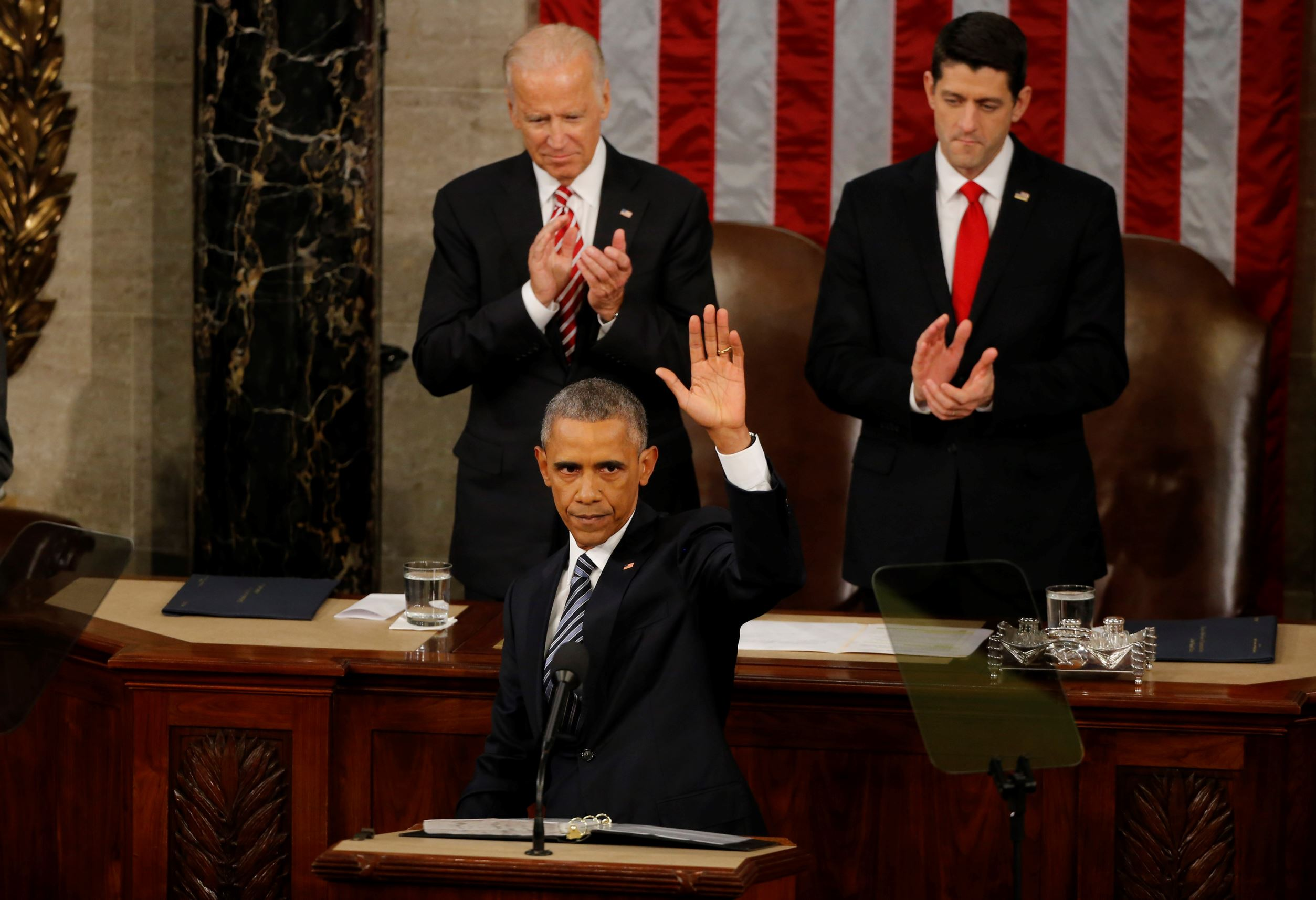 U.S. Vice President Joe Biden (L, rear) and Speaker of the House Paul Ryan (R, rear) applaud as U.S. President Barack Obama waves at the conclusion of his State of the Union address to a joint session of Congress in Washington, January 12, 2016.