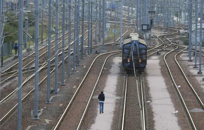 Un migrant marche entre les voies de chemin de fer sur le site d'Eurotunnel à Coquelles, près de Calais.