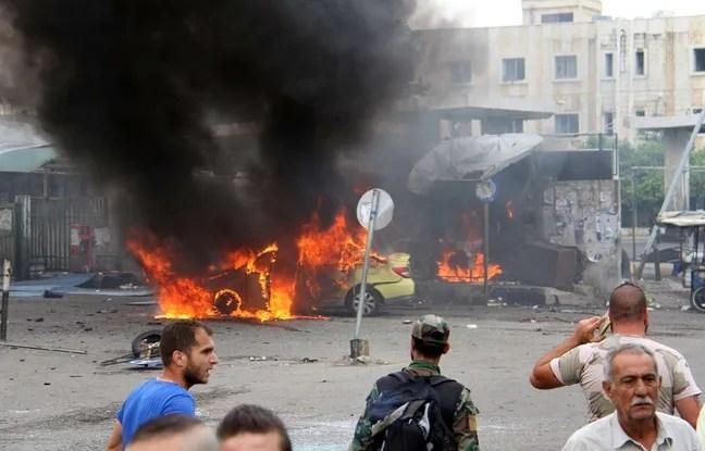 Une photo de l'agence SANA qui montre des Syriens devant une voiture en feu après une attaque à Tartus en Syrie le 23 mai 2016.
