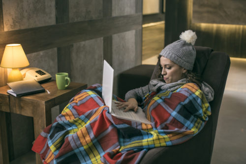 Women wearing winter cap working on laptop wrapped in a blanket at home with no heating