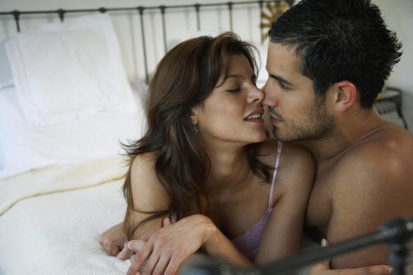 Hispanic couple kissing on bed