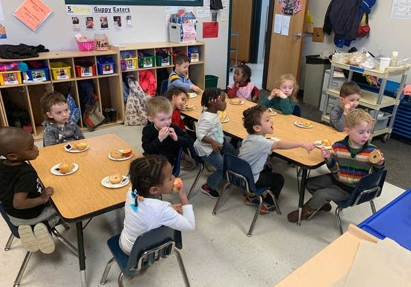 Children sit around tables.