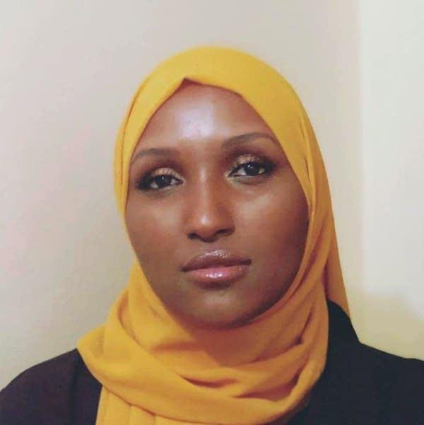 A woman wearing a yellow hijab and black shirt.