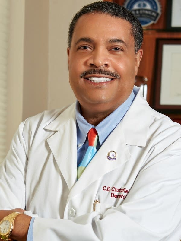 A man wearing a white doctor's jacket.