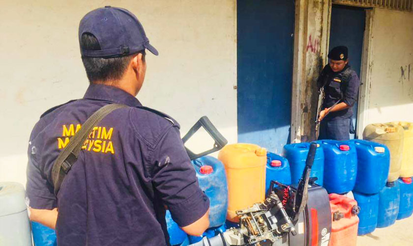 Sebahagian tong berisi minyak petrol dan enjin bot yang dirampas APMM.