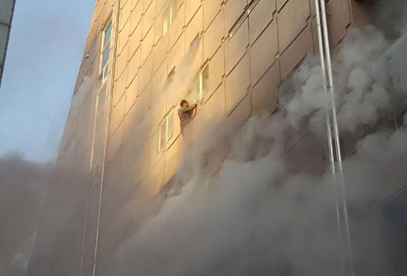 A survivor dangles from a windowsill as he waits for rescue from the burning building on Dec 21, 2017. - REUTERS