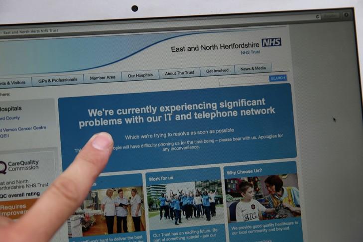 Une femme montre le site Web du NHS (East and North Hertfordshire), informant les utilisateurs d'un problème dans son réseau, à Londres le 12 mai 2017 / AFP
